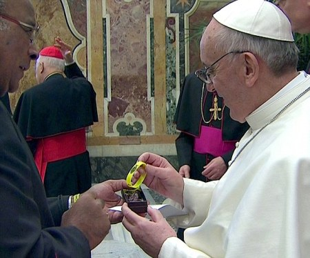 Newly elected Pope Francis is given a yellow Catholic faith bracelet following a meeting at the Vatican