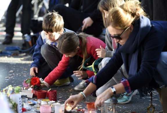 Children and adults lay flowers and light candles at a shift memorial along a police cordon set-up close to the Bataclan concert hall on November 15, 2015 in Paris, following a series of coordinated attacks in and around Paris on November 13. Islamic State jihadists claimed a series of coordinated attacks by gunmen and suicide bombers in Paris that killed at least 129 people and wounded hundreds more in scenes of carnage at a concert hall, restaurants and the national stadium.  AFP PHOTO / MIGUEL MEDINA        (Photo credit should read MIGUEL MEDINA/AFP/Getty Images)